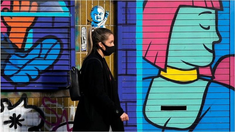 woman in mask walking in front of graffiti, Getty images