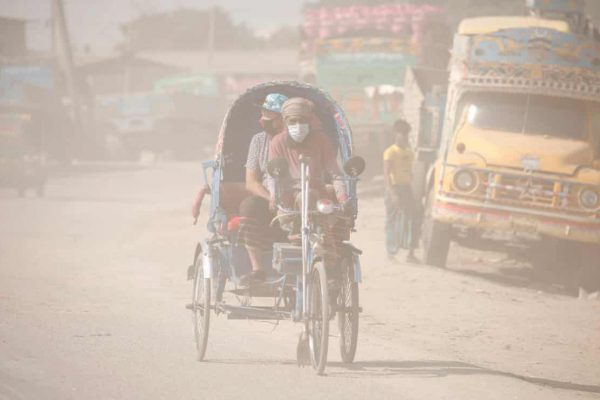 Two men on transport through smoggy road