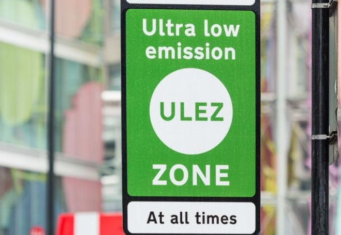 Green sign with white text reading 'Ultra low emission zone'. Smaller black text on white background 'At all times'
